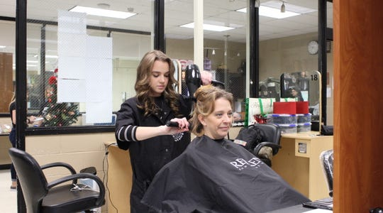 SCVTHS Cosmetology student Katie Acheson of Bridgewater performs a hair treatment at the annual Holiday Cut-A-Thon & Toy Drive on Saturday, Dec.7.