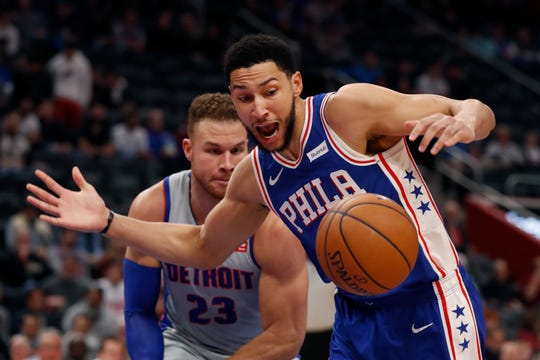 Detroit Pistons forward Blake Griffin (23) and Philadelphia 76ers guard Ben Simmons (25) chase the loose ball during the first half of an NBA basketball game, Monday, Dec. 23, 2019, in Detroit. (AP Photo/Carlos Osorio)