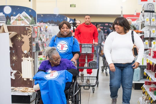 Pistons guard Tim Frazier, back, and his mother, Janice, left, walk through the Meijer in Detroit with Nakiya Hamilton, right, with her mother, Rosa, on Dec. 22, 2019.