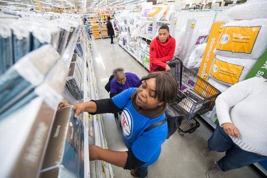 Pistons guard Tim Frazier, back, watches as his mother, Janice, grabs an item in the Meijer in Detroit on Dec. 22, 2019.