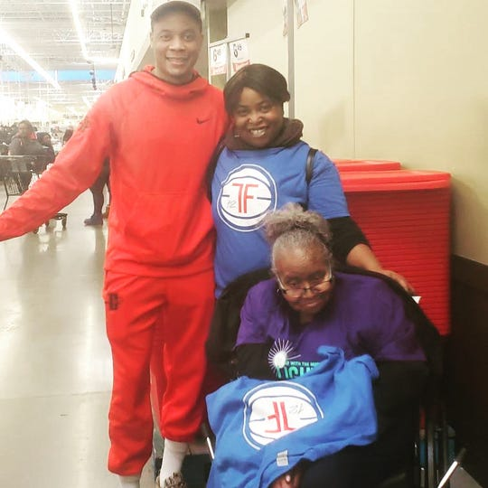 Pistons guard Tim Frazier and his mother, Janice, pose with Rosa Hamilton at the Meijer in Detroit on Dec. 22, 2019.