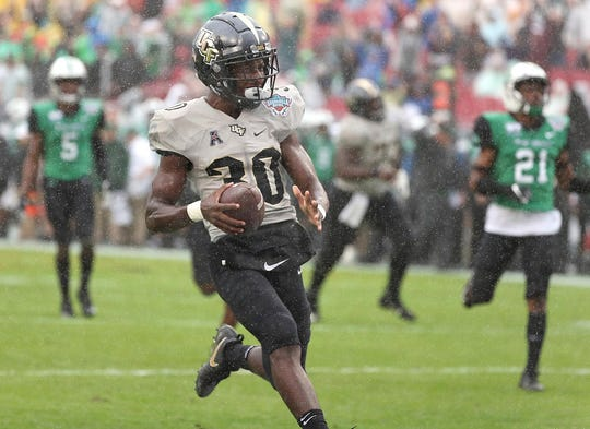 Central Florida running back Greg McCrae leaves Marshall defenders behind on a touchdown run during the Gasparilla Bowl on Monday.