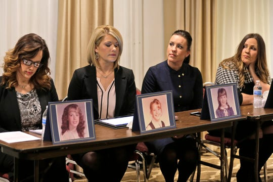 Sisters Patty Fortney-Julius, Lara Fortney McKeever, second from left, Teresa Forteny-Miller, second from right, and Carolyn Fortney sit behind pictures of themselves as children as they listen to an attorney speak to reporters during a news conference in Newark, N.J., Monday, Dec. 2, 2019.