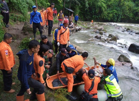 In this photo released by the National Search And Rescue Agency (BASARNAS), rescuers remove the body of a victim of a bus accident in Pagaralam, Indonesia, Tuesday, Dec. 24, 2019.