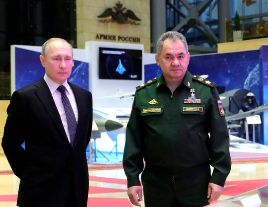 Russian President Vladimir Putin, left, and Defense Minister Sergei Shoigu speaks to journalists after attending an annual meeting with top military officials in the National Defense Control Center in Moscow, Russia, Tuesday, Dec. 24, 2019.