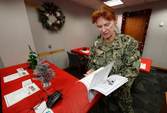 United States Navy Specialist Petty Officer 1st Class Shannon Chambers of Long Beach, Calif., looks over a volunteer playbook in the NORAD Tracks Santa center at Peterson Air Force Base, Monday, Dec. 23, 2019, in Colorado Springs, Colo.