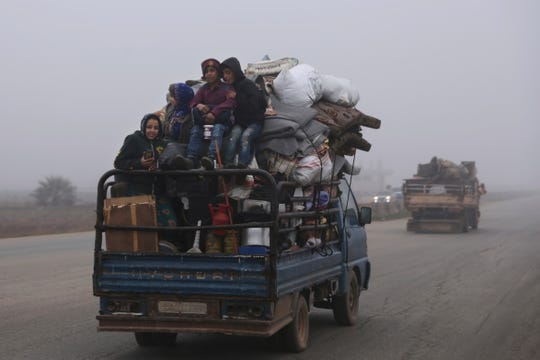 Civilians ride in a truck as they flee Maaret al-Numan, Syria, ahead of a government offensive, Monday, Dec. 23, 2019.