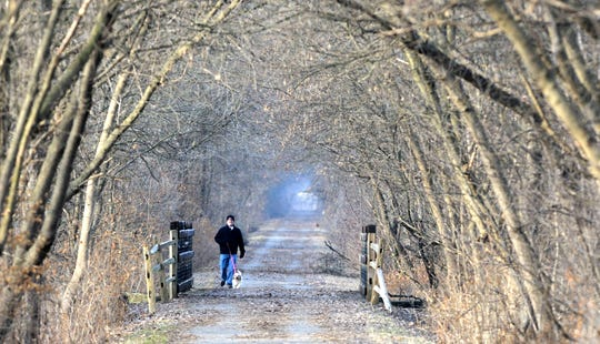 Steve Conroy, of Armada, takes a walk with 'Paisley,' his four-year-old female Cavalier King Charles Spaniel mix, as they walk east on the Macomb Orchard Hike Bike Trail in Armada, Tuesday, December 24 2019.
