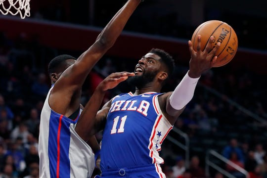 Philadelphia 76ers forward James Ennis III (11), defended by Detroit Pistons guard Tony Snell, attempts a layup during the first half Monday.