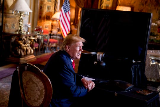President Donald Trump speaks to members of the media following a Christmas Eve video teleconference with members of the military at his Mar-a-Lago estate in Palm Beach, Fla., Tuesday, Dec. 24, 2019.
