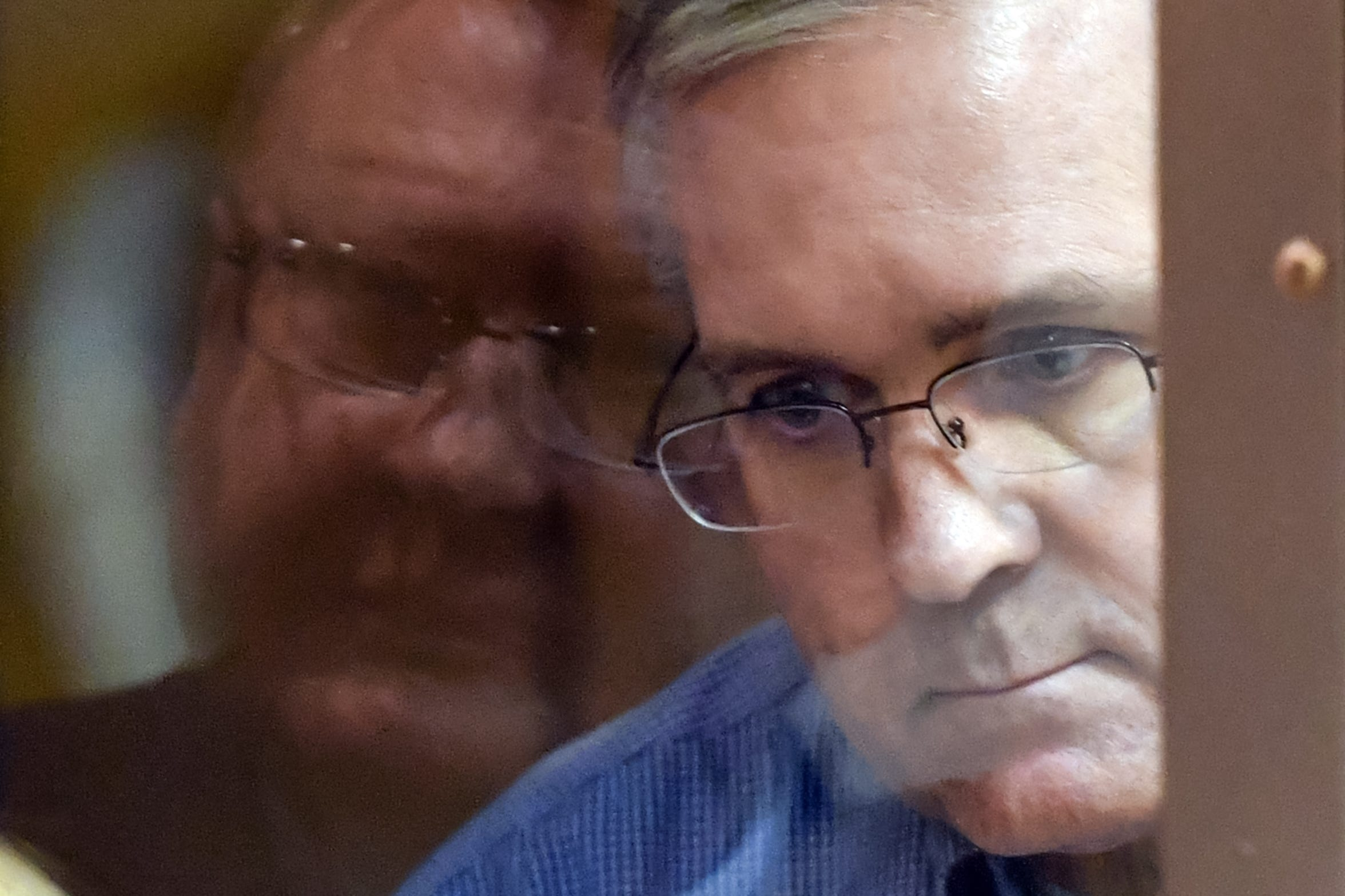 Paul Whelan listens to his lawyers while standing inside a defendants' cage during a hearing at a court in Moscow earlier this year.