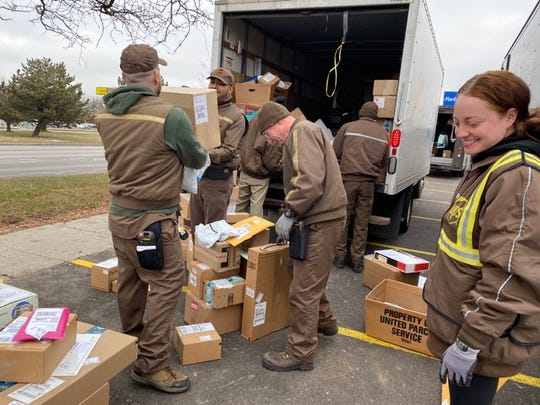 Samantha Navarre, right, and other UPS drivers unload packages to be delivered for Christmas outside a Kroger store in Dearborn on Tuesday, Dec. 24, 2019.