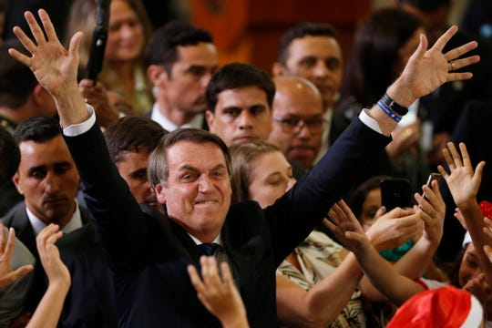 Brazil's President Jair Bolsonaro waves to the crowd during a Christmas celebration with staff and students at the Planalto Presidential Palace, in Brasilia, Brazil, Thursday, Dec. 19, 2019.