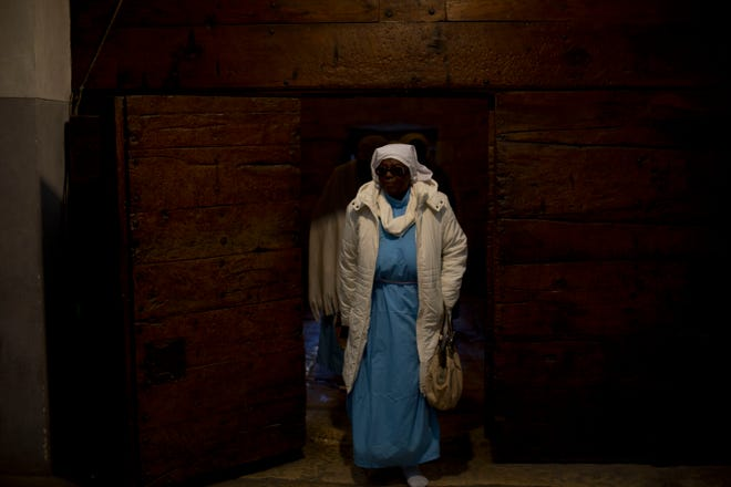 A Christian pilgrim from Nigeria enters the Church of the Nativity, built on top of the site where Christians believe Jesus Christ was born, on Christmas Eve in the West Bank City of Bethlehem, Tuesday, Dec. 24, 2019.