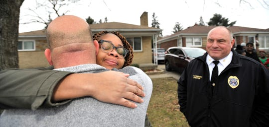 Domestic violence survivor Kaitlyn Jolly hugs Center Line Detective Danny Petroff, left, as public safety director Paul Myszenski, right, watches the emotional moment.