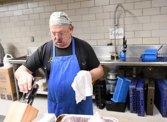 Volunteer Jack Kahn handles the dishwashing during dinner preparation  Dec. 22, 2019 at Congregation Beth Shalom in Oak Park.
