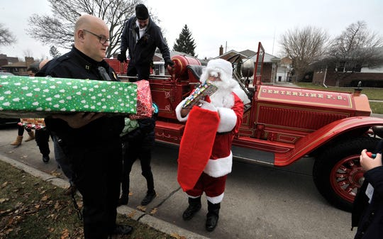 Center Line Police Reserve Capt. John Turpin, left, helps reserve police officer Greg Taylor, aka Santa, with Christmas presents as division fire chief Charles Schubert, center, climbs off a 1926 American LaFrance fire truck.