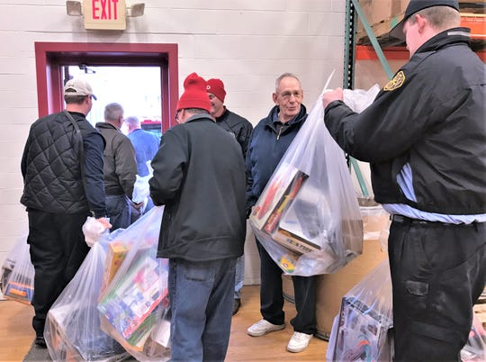 Volunteers from the Village of Horseheads Fire Department carry gift bags from Arctic League headquarters in Elmira out to waiting trucks Tuesday morning for Christmas delivery to families in rural areas of Chemung County.