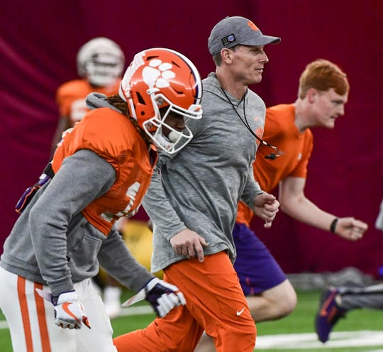 Clemson Defensive Coordinator Brent Venables runs with safety Denzel Johnson (14) during practice in Tempe, Arizona Tuesday, December 24.