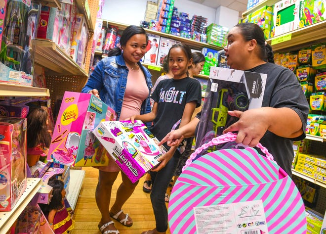 From left: Keana Evangelista, Jae'Shauna Evangelista and JaeRose Quitugua shop for last minute Christmas gifts at the KD Toys store in the Micronesia Mall on Tuesday, Dec. 24, 2019.