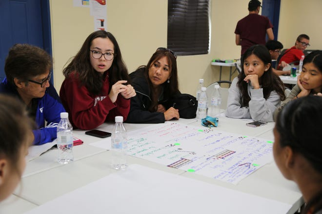 Aya Cathey, center, in red, leads a group discussion during the 2019 Year-End Referees Seminar held Saturday at the Guam Football Association National Training Center Lecture Hall.