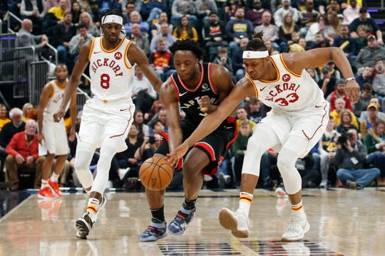 Indiana Pacers center Myles Turner (33) and Toronto Raptors forward OG Anunoby (3) chase after a loose ball during the first quarter at Bankers Life Fieldhouse.