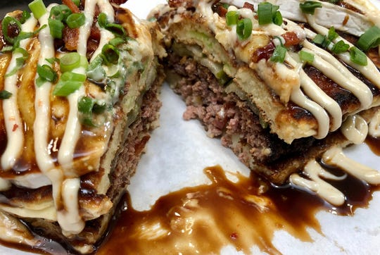 """The half-pound smashed burger, a blend of beef chuck, brisket and heart, plus pork fat, will land on the Japanese pancake called """"okonomiyaki"""" instead of a bun at Lil' Dumplings, one of the new restaurants the Indianapolis area will see in 2020. The burger is dressed with yuzu kosho mayonnaise, local Tulip Tree trillium cheese, Smoking Goose bacon bits, cucumber pickles and traditional okonomiyaki sauce containing ketchup and Worcestershire sauce."""