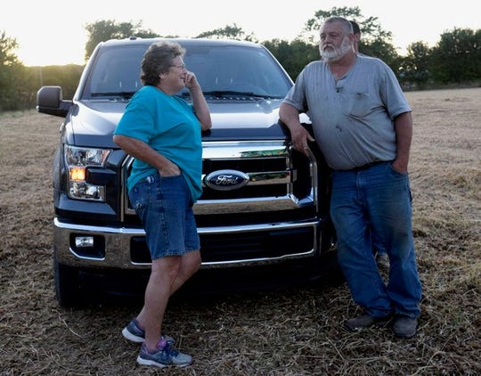 """June and Jeff Deck discuss transporting soybeans to their distributor. The process requires getting up before the sun rises and driving their semitruck 45 minutes to the drop-off location. Jeff and June have raised two children on their Ellettsville farm. Farming is not easy, June says, but they have to keep going. """"We're farmers,"""" she says. """"That's what we are for life."""""""