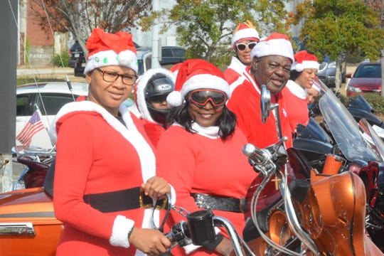 Helen Brown, left, Karen Berry and Eddie Carson park their motorcycles in front of the Welcome to Jackson sign at the intersection of Pearl and State streets in Jackson, Miss., on Dec. 24, 2019. The three are part of a biker group called Friends of Fallen Riders. Every Christmas season, they deliver toys and other presents to children in high-poverty areas in the city.