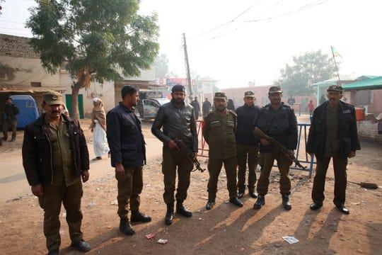 Pakistani police officers stand guard outside Multan in Multan, Pakistan, Saturday, Dec. 21, 2019. A Pakistani court on Saturday convicted Muslim professor Junaid Hafeez of blasphemy, sentencing him to death for allegedly spreading anti-Islamic ideas.