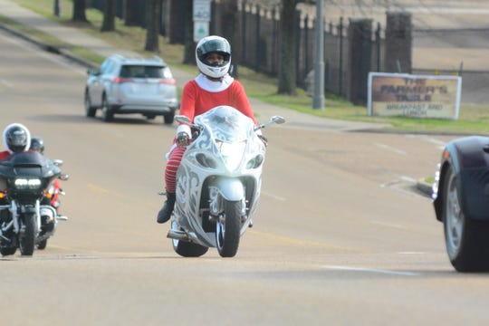 Members of the Jackson area motorcycle group Friends of Fallen Riders, dressed up for Christmas, drive through Jackson on Dec. 24, 2019, to hand out presents to children in impoverished areas of the city.