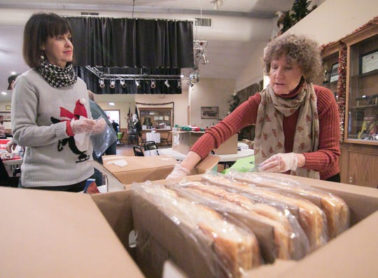 Sandy Hatfield, left, and Susan Ellithorpe package buns Tuesday, Dec. 24, 2019 to be delivered on Christmas Day as one of the special Meals on Wheels preparations.
