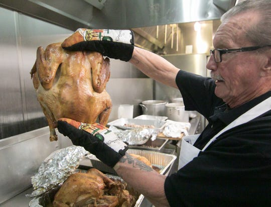 American Legion Devereaux Post 141 chef Tom Stone holds one of a number of turkeys Tuesday, Dec. 24, 2019 being prepared in partnership with Meals on Wheels for a Christmas meal for homebound seniors.