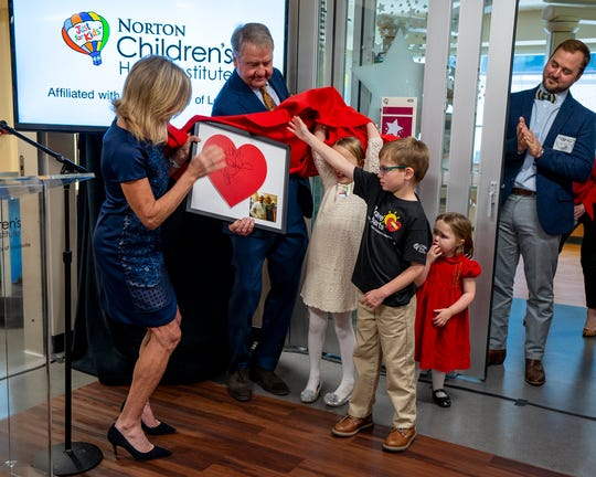 Karen and Gary Lawrence held a heart signed by their daughter, actress Jennifer Lawrence, at the Jennifer Lawrence Cardiac Intensive Care Unit dedication. Children helping are Jonathan Young, center, Frances Bumpas, left and Jane Bumpas (right, in red dress).