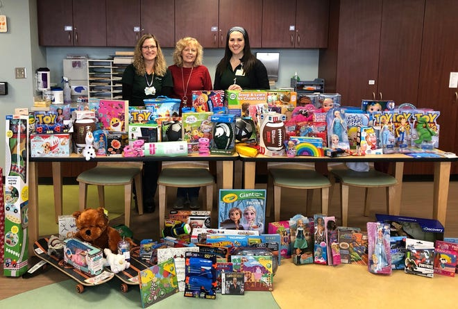 RE/MAX agents pose with the mountain of gifts they donated to children at Sparrow Children's Center.