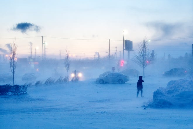 A pedestrian walks through the blowing snow in the Frandor parking lot on Tuesday, Jan. 29, 2019, in Lansing.