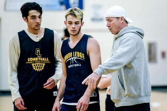 Comets assistant basketball coach Todd Hastings, right, instructs players Bobby Rao, left, and Brayden Denny during practice on Monday, Dec. 23, 2019, at Grand Ledge High School. Friends and community members are raising money to support the Hastings family and their three young children, while Todd is treated for cancer.