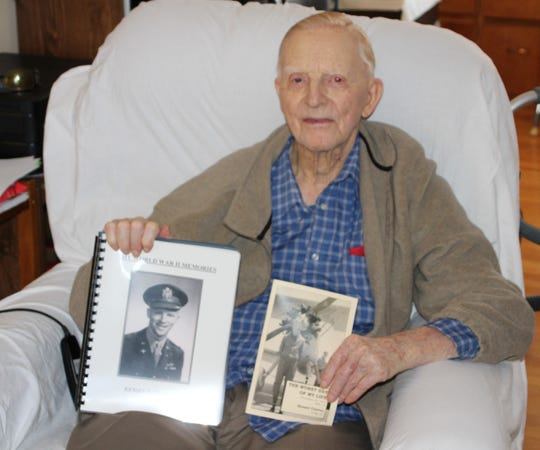 World War II veteran Kensel E. Clutter displays two books he wrote about his experiences during the war. He served as a B-24 bomber pilot in the United States Army Air Force. Clutter's books are available through the Marion County Historical Society.