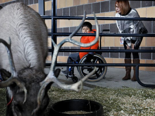 Christopher Herrera Mauricio 8 along with Pattie Austin a tutor at Colerain Elementary School December 17, 2019 look at the reindeer. Dan Downs of Pine Acres Farm in LaRue visits the school every two years with his reindeer.