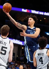 Grizzlies forward Brandon Clarke lays the ball up over over the San Antonio Spurs' Jakob Poeltl, left, and Derrick White on Dec. 23.