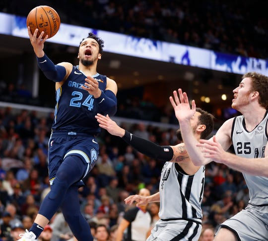 Memphis Grizzlies guard Dillon Brooks lays the ball up past San Antonio Spurs guard Marco Belinelli and center 	Jakob Poelt during their game at the FedExForum on Monday, Dec. 23, 2019.