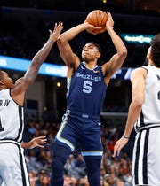 Memphis Grizzlies forward Bruno Caboclo shoots the ball over San Antonio Spurs guards Lonnie Walker IV, left, and Derrick White during their game at the FedExForum on Monday, Dec. 23, 2019.