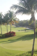 Players in the South Collier YMCA (Marco) annual golf tournament fundraiser finish up on the beautiful 18th hole at Hammock Bay.