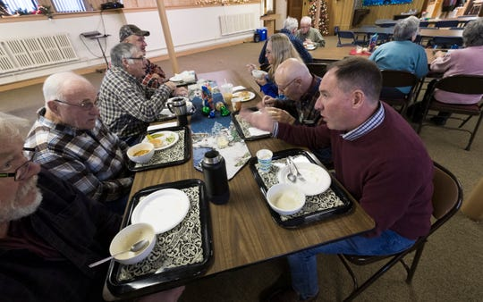 """Dairy farmer Randy Roecker, right, talks with retired dairy farmer Hank Elfers, second from left, at St. Peter's Lutheran Church in Loganville. Roecker helped organize """"Farm Neighbors Care"""" events to help farmers who need support."""