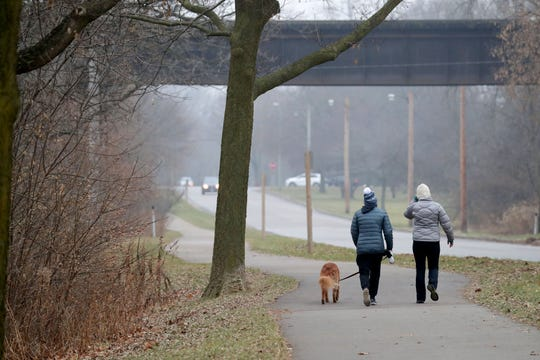 People walk along a walking trail on North River Parkway near Kletzsch Park in Glendale on Tuesday, Dec. 24, 2019.