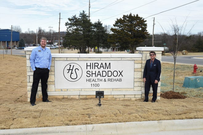 Hiram Shaddox Health & Rehab officials (from left) administrator Ben Worlow and medical director Dr. Tim Paden stand next to the Hiram Shaddox sign at the entrance to the building's parking lot. Hiram Shaddox Health & Rehab will open in January as the successor to Hiram Shaddox Geriatric Health and Rehab, which closed in 2018 after being damaged in a storm.