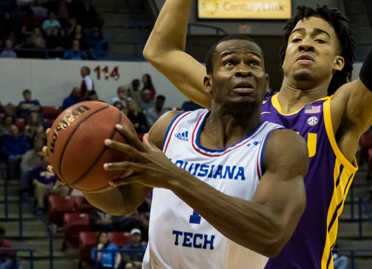 Louisiana Tech' Derric Jean (1) drives a lane against Louisiana State University's Caleb Starks (20) dunks during the exhibition game against at the Thomas Assembly Center in Ruston, La. on Nov. 2. Proceeds from the game would go towards relief efforts from the April 25 tornado in Ruston.