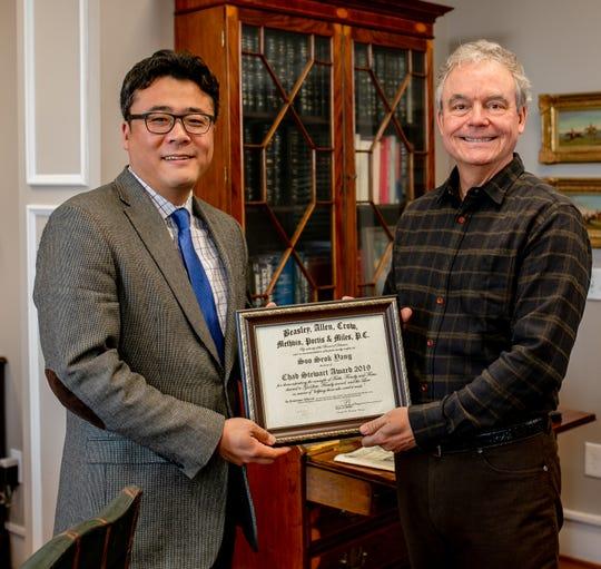 Beasley Allen attorney Soo Seok Yang receives the Chad Stewart Award from Principal and Managing Attorney Tom Methvin.