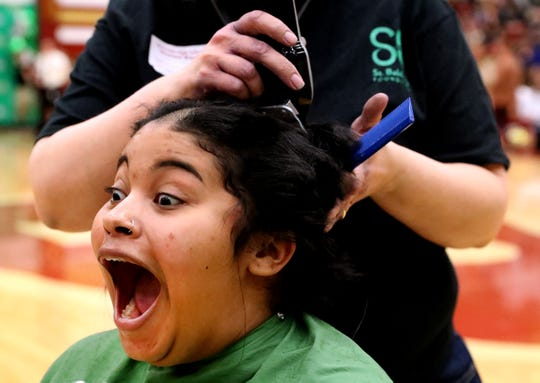Arial Witty Floyd reacts as she gets her head shaved during Riverdale High School's sixth annual Brave the Shave fundraiser to benefit St. Baldrick's Foundation on Thursday, March 21, 2019. The organization raises funds and awareness for childhood cancer.
