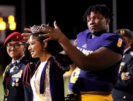 Smyrna's Dallas Walker (8) crowns  Homecoming Queen Amani Colon as Colon's attendant, Smyrna JROTC member Rey Vongboupha, looks on during halftime of the homecoming game against Riverdale at Smyrna on Friday, Sept. 13, 2019.